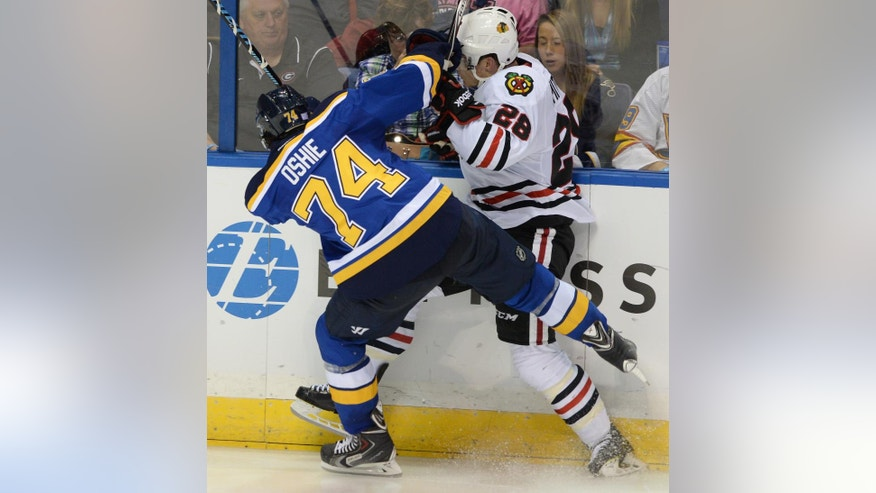 St. Louis Blues' T.J. Oshie checks Chicago Blackhawks' Ben Smith (28) during the second period of an NHL hockey game, Saturday, Oct. 25, 2014, in St. Louis. (AP Photo/Bill Boyce)