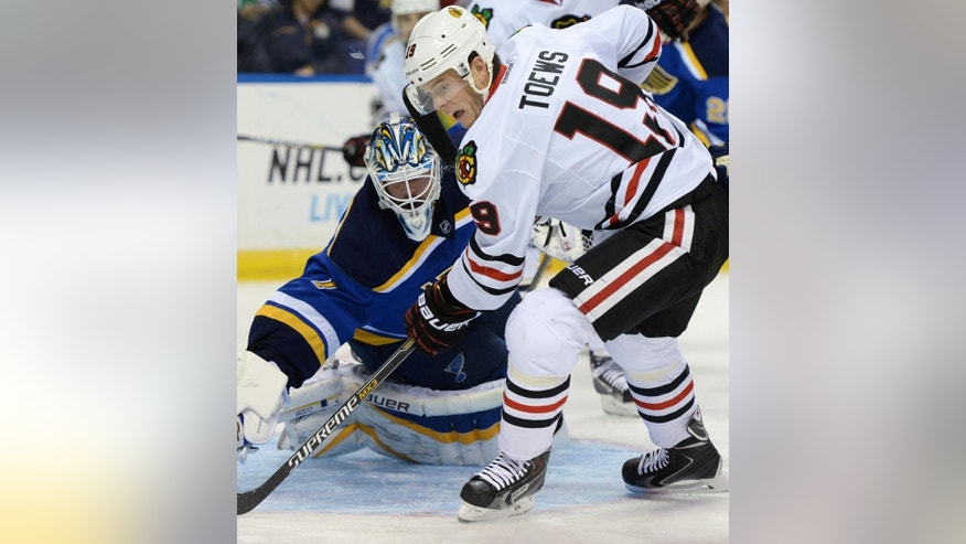 St. Louis Blues goalie Brian Elliott (1) defends Chicago Blackhawks' Jonathan Toews (19) during the first period of an NHL hockey game, Saturday, Oct. 25, 2014, in St. Louis. (AP Photo/Bill Boyce)