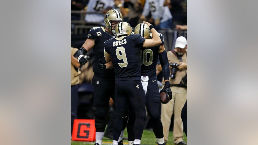 New Orleans Saints tight end Jimmy Graham (80) celebrates his touchdown reception with quarterback Drew Brees (9) and tackle Zach Strief, left, in the second half of an NFL football game against the Green Bay Packers in New Orleans, Sunday, Oct. 26, 2014. (AP Photo/Rogelio Solis)