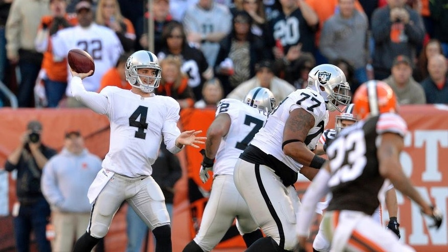 Oakland Raiders quarterback Derek Carr (4) pass for a first down against the Cleveland Browns in the second quarter of an NFL football game, Sunday, Oct. 26, 2014, in Cleveland. (AP Photo/David Richard)
