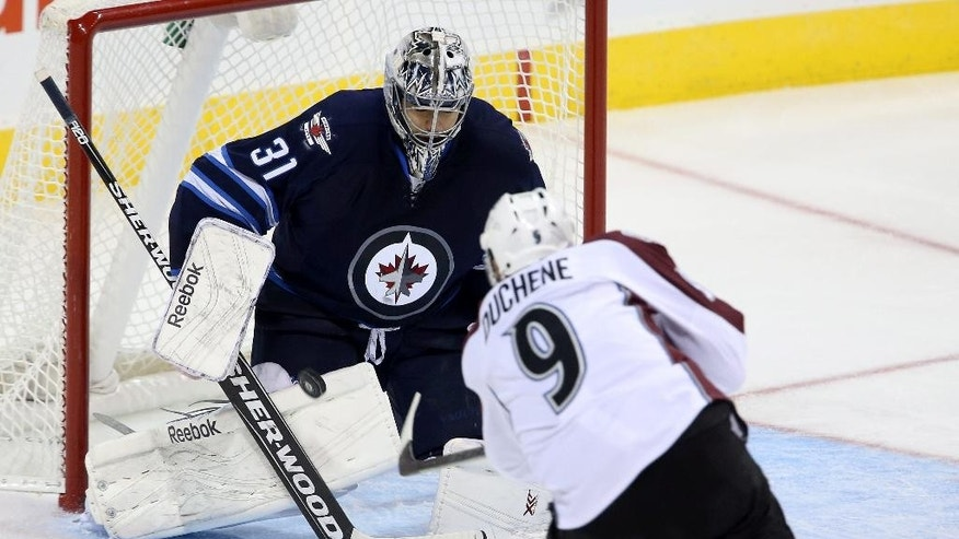 Winnipeg Jets goaltender Ondrej Pavelec (31) saves a shot by Colorado Avalanche's Matt Duchene (9) during second period NHL hockey action in Winnipeg, Manitoba, Sunday, Oct. 26, 2014. (AP Photo/The Canadian Press, Trevor Hagan)