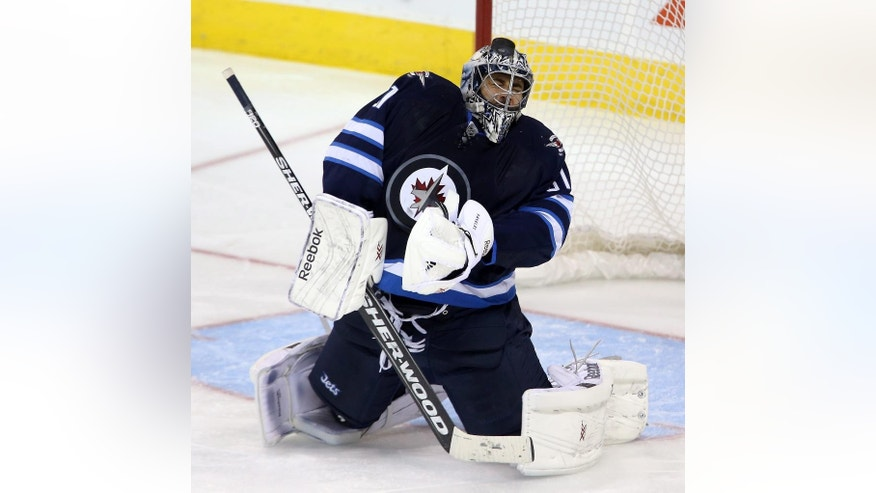 Winnipeg Jets goaltender Ondrej Pavelec (31) is hit in the mask by a shot from the Colorado Avalanche during third period NHL hockey action in Winnipeg, Manitoba, Sunday, Oct. 26, 2014. (AP Photo/The Canadian Press, Trevor Hagan)