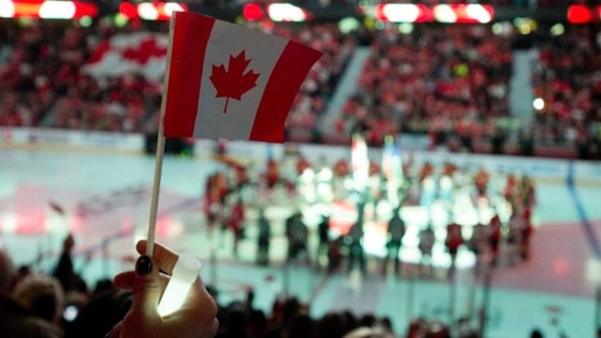 October 25, 2014: A woman holds up a Canadian flag as the national anthem is played during pre-game ceremonies at the NHL game between the Ottawa Senators and New Jersey Devils. (AP Photo/The Canadian Press, Adrian Wyld)