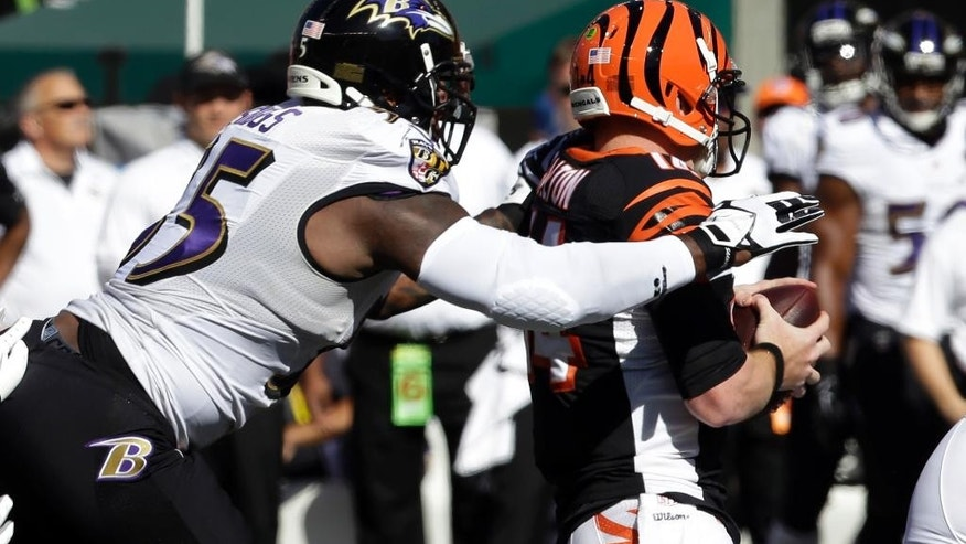 Baltimore Ravens outside linebacker Terrell Suggs, left, sacks Cincinnati Bengals quarterback Andy Dalton during the first half of an NFL football game in Cincinnati, Sunday, Oct. 26, 2014. (AP Photo/Al Behrman)