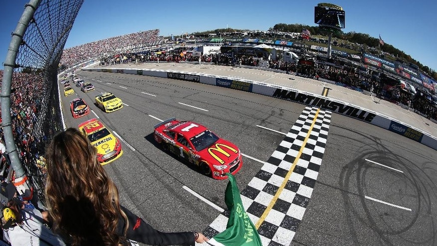 In this photo provided by NASCAR and taken with a fisheye lens, Jamie McMurray (1) and Joey Logano, (22) lead the field to the green flag for the running of the NASCAR Sprint Cup Series auto race at Martinsville Speedway, Sunday, Oct. 26, 2014, in Martinsville, Va. (AP Photo/NASCAR, Sarah Glenn)
