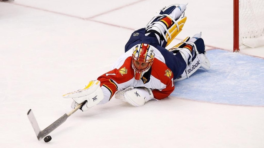 Florida Panthers' Roberto Luongo dives for the puck to make a save against the Arizona Coyotes during the first period of an NHL hockey game Saturday, Oct. 25, 2014, in Glendale, Ariz. (AP Photo/Ross D. Franklin)