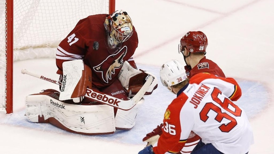 Arizona Coyotes' Mike Smith (41) makes a save on a shot by Florida Panthers' Jussi Jokinen (36), of Finland, as Coyotes' Michael Stone (26) also defends during the first period of an NHL hockey game Saturday, Oct. 25, 2014, in Glendale, Ariz. (AP Photo/Ross D. Franklin)