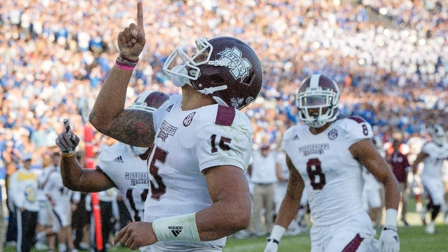 Mississippi State quarterback Dak Prescott celebrates after running for a touchdown during the second half of an NCAA college football game against Kentucky at Commonwealth Stadium in Lexington, Ky., Saturday, Oct. 25, 2014. Mississippi State won 45-31. (AP Photo/David Stephenson)