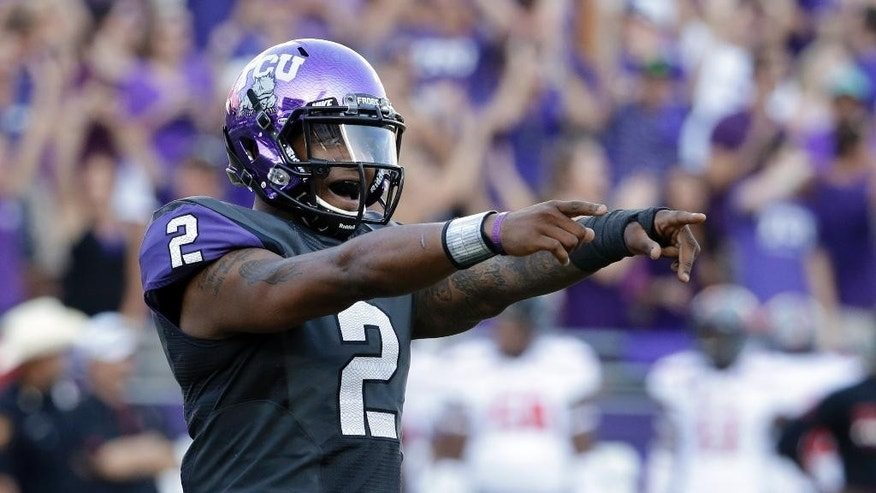 TCU's Trevone Boykin (2) points to the sideline after throwing a touchdown pass in the second half of an NCAA college football game against Texas Tech, Saturday, Oct. 25, 2014, in Fort Worth, Texas. Boykin was 22 of 39 for 433 yards while setting a career high in yards passing for the second week in a row in the 82-27 TCU win. (AP Photo/Tony Gutierrez)