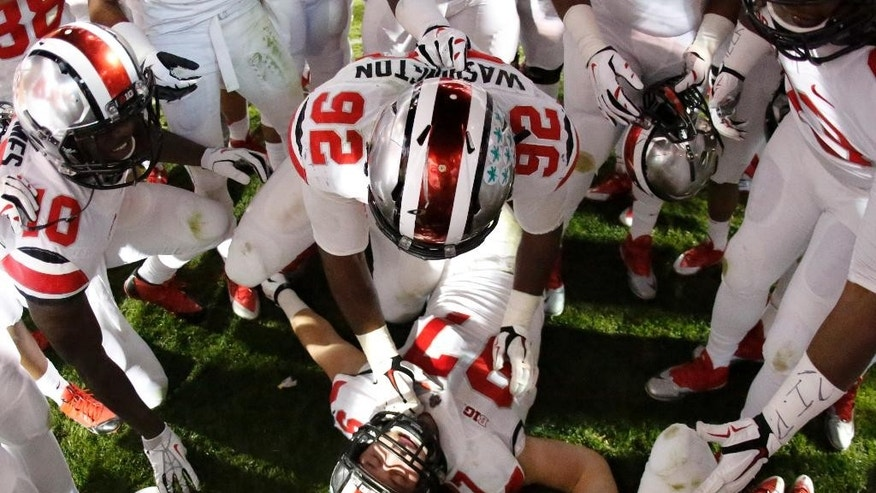 Ohio State defensive lineman Joey Bosa (97) is surrounded by teammates as they celebrate a 31-24 win in double overtime against Penn State in an NCAA college football game in State College, Pa., Sunday, Oct. 26, 2014. (AP Photo/Gene J. Puskar)