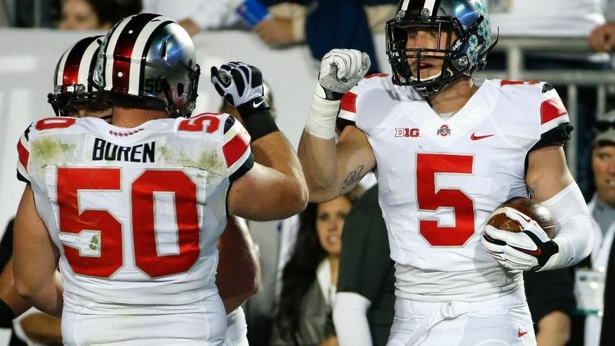 Ohio State tight end Jeff Heuerman (5) celebrates with offensive lineman Jacoby Boren (50) after scoring on a pass from quarterback J.T. Barrett during the second quarter an NCAA college football game against Penn State in State College, Pa., Saturday, Oct. 25, 2014. (AP Photo/Gene J. Puskar)