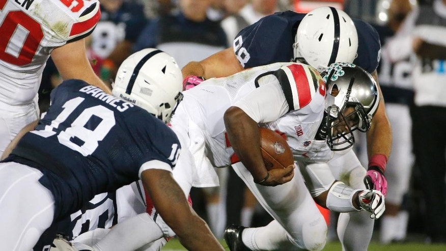 Ohio State quarterback J.T. Barrett (16) is brought down after a short gain by Penn State defensive end Deion Barnes (18) and defensive tackle Anthony Zettel, rear, during the second quarter an NCAA college football game in State College, Pa., Saturday, Oct. 25, 2014. (AP Photo/Gene J. Puskar)