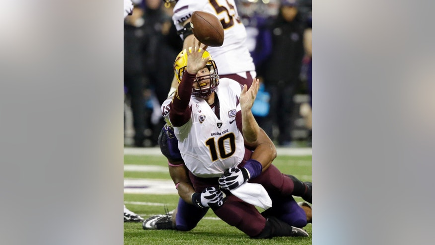 Arizona State quarterback Taylor Kelly tries to get off a pass while being brought down by Washington's Andrew Hudson during the first half of an NCAA college football game Saturday, Oct. 25, 2014, in Seattle. (AP Photo/Elaine Thompson)