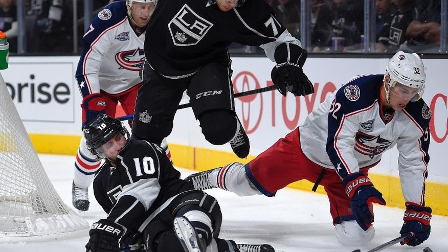 Columbus Blue Jackets right wing Adam Cracknell, right, falls as he battles for the  puck with center Mike Richards, loser left, and center Jordan Nolan, center, while defenseman Jack Johnson looks on during the second period of an NHL hockey game, Sunday, Oct. 26, 2014, in Los Angeles. (AP Photo/Mark J. Terrill)