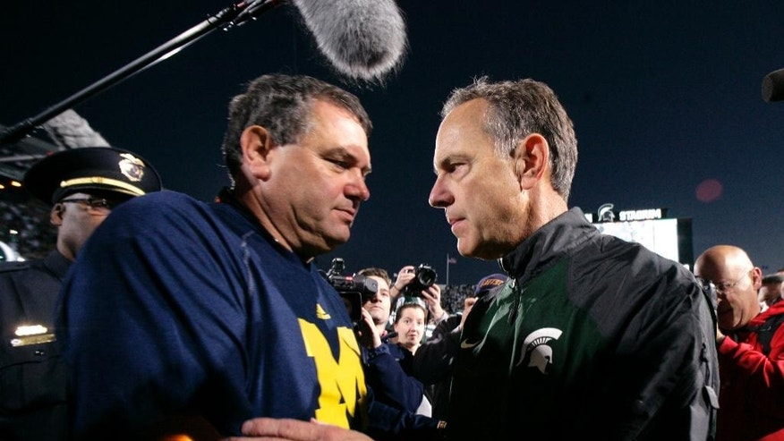 Michigan coach Brady Hoke, left, and Michigan State coach Mark Dantonio shake hands following an NCAA college football game, Saturday, Oct. 25, 2014, in East Lansing, Mich. Michigan State won 35-11. (AP Photo/Al Goldis)