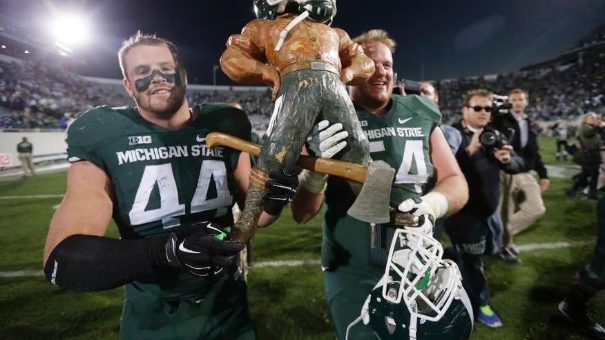 Michigan State defensive end Marcus Rush (44) and guard Connor Kruse (54) carry off the Paul Bunyan trophy after their 35-11 win over in an NCAA college football game in East Lansing, Mich., Saturday, Oct. 25, 2014. (AP Photo/Carlos Osorio)
