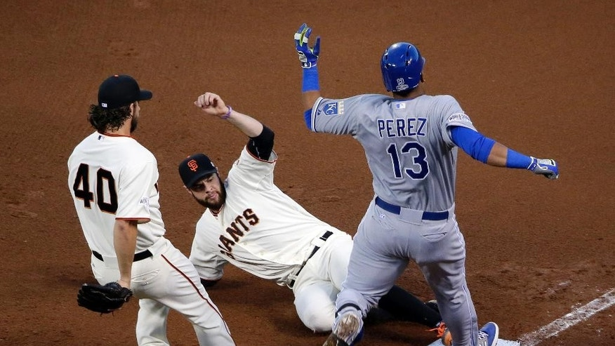 Kansas City Royals' Salvador Perez is out at first on the sliding tag of San Francisco Giants' Brandon Belt (9) Madison Bumgarner moves in to assist, during the fourth inning of Game 5 of baseball's World Series Sunday, Oct. 26, 2014, in San Francisco. (AP Photo/Marcio Jose Sanchez)