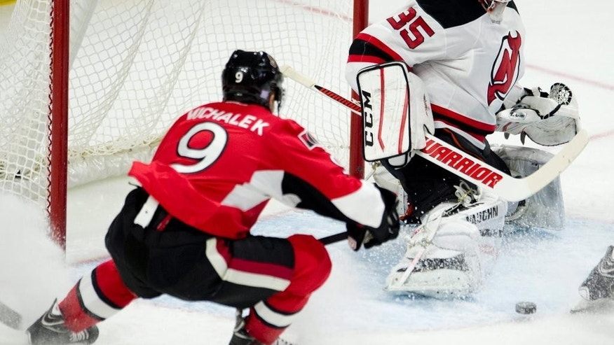 New Jersey Devils goalie Cory Schneider makes a save on Ottawa Senators left wing Milan Michalek during the first period of an NHL hockey game, Saturday, Oct. 25, 2014 in Ottawa, Ontario. (AP Photo/The Canadian Press, Adrian Wyld)