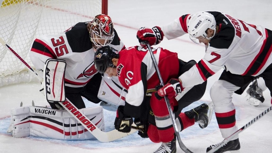 New Jersey Devils defenseman Jon Merrill pushes Ottawa Senators right wing Alex Chiasson over the puck as Devils goalie Cory Schneider looks on during first period of an NHL hockey game, Saturday, Oct. 25, 2014 in Ottawa, Ontario. (AP Photo/The Canadian Press, Adrian Wyld)