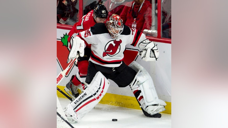 New Jersey Devils goalie Cory Schneider collides with Ottawa Senators right wing Curtis Lazar along the boards as he plays the puck during the second period of an NHL hockey game, Saturday, Oct. 25, 2014 in Ottawa, Ontario. (AP Photo/The Canadian Press, Adrian Wyld)