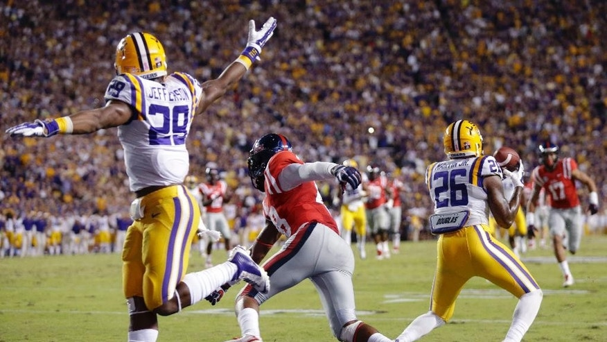 LSU safety Ronald Martin (26) intercepts a pass that was intended for Mississippi wide receiver Cody Core (88) in the second half of an NCAA college football game in Baton Rouge, La., Saturday, Oct. 25, 2014. At left is LSU's Rickey Jefferson. LSU won 10-7. (AP Photo/Gerald Herbert)