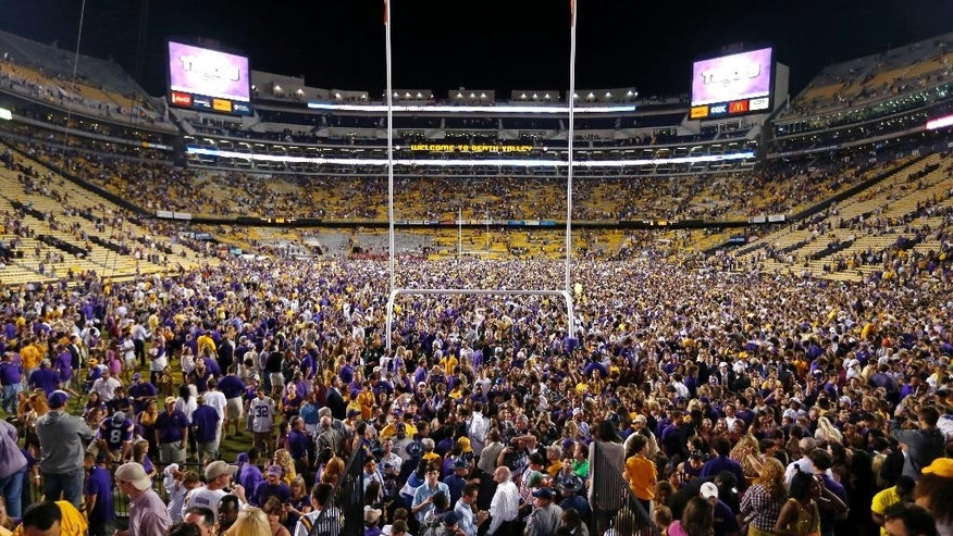LSU fans swarm the field after their victory over Mississippi in an NCAA college football game in Baton Rouge, La., Saturday, Oct. 25, 2014. LSU won 10-7. (AP Photo/Jonathan Bachman)