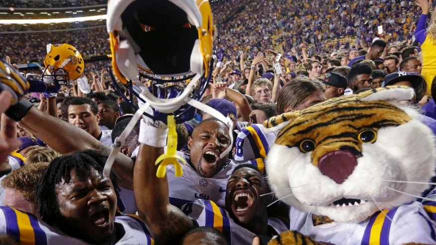 LSU players celebrate with swarming fans after defeating Mississippi in an NCAA college football game in Baton Rouge, La., Saturday, Oct. 25, 2014. LSU won 10-7. (AP Photo/Gerald Herbert)