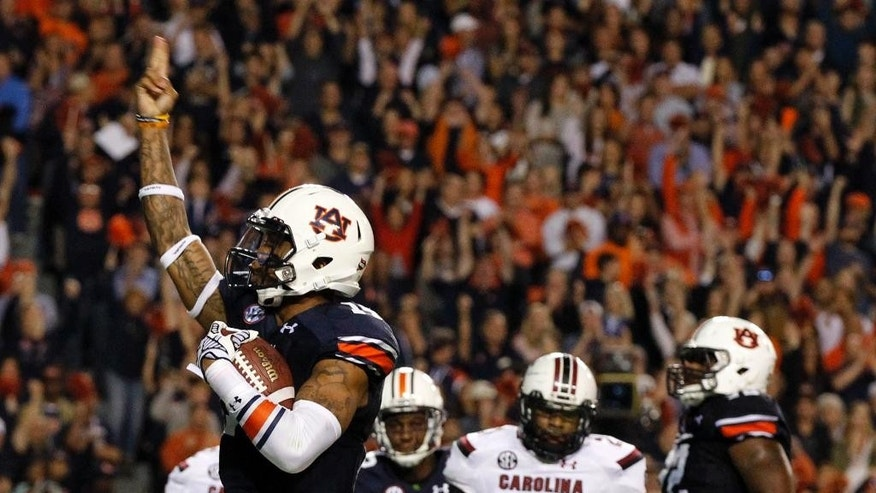 Auburn quarterback Nick Marshall (14) celebrates after scoring a touchdown during the second half of an NCAA college football game against South Carolina on Saturday, Oct. 25, 2014, in Auburn, Ala. Auburn won 42-35. (AP Photo/Butch Dill)