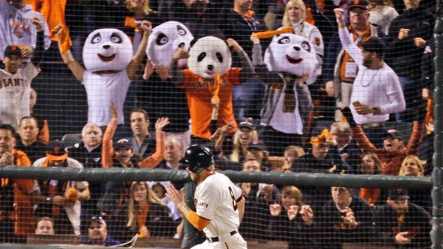 San Francisco Giants' Hunter Pence heads for home to score on a single by Brandon Belt during the sixth inning of Game 4 of baseball's World Series against the Kansas City Royals on Saturday, Oct. 25, 2014, in San Francisco. (AP Photo/Charlie Riedel)