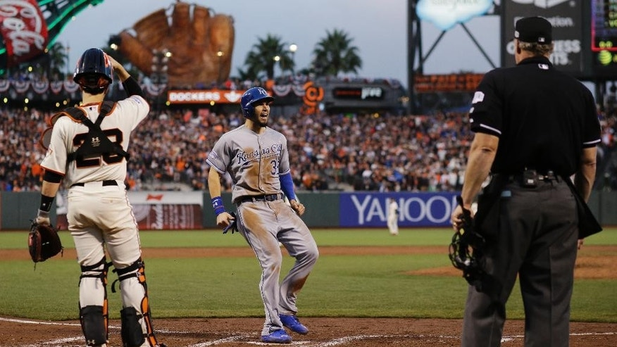Home plate umpire Hunter Wendelstedt and San Francisco Giants catcher Buster Posey watch as Kansas City Royals Eric Hosmer scores on an RBI single by Salvador Perez during the third inning of Game 4 of baseball's World Series Saturday, Oct. 25, 2014, in San Francisco. Lorenzo Cain also scored on the hit. (AP Photo/David J. Phillip)
