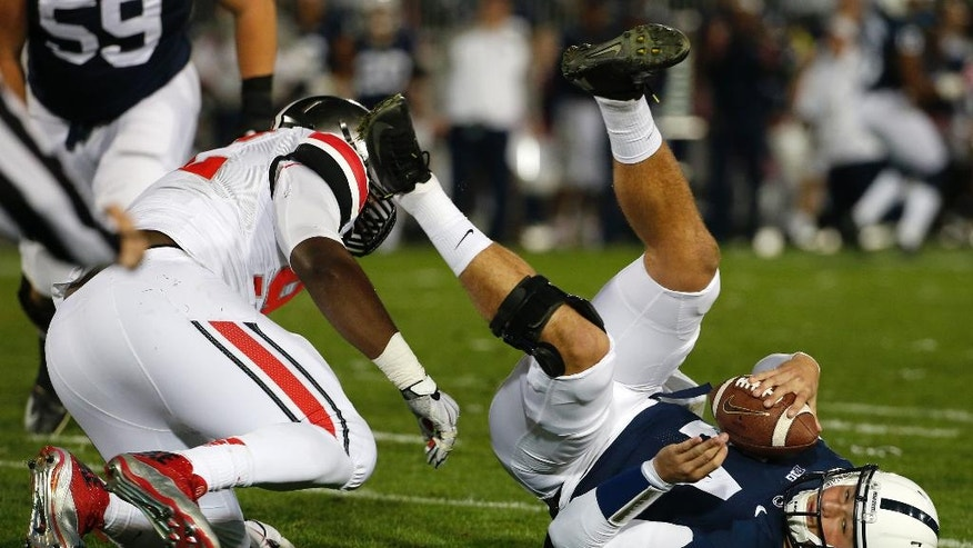 Penn State quarterback Christian Hackenberg (14) is sacked by Ohio State defensive lineman Adolphus Washington during the fourth quarter an NCAA college football game in State College, Pa., Saturday, Oct. 25, 2014. Ohio State won 31-24 in two overtimes. (AP Photo/Gene J. Puskar)