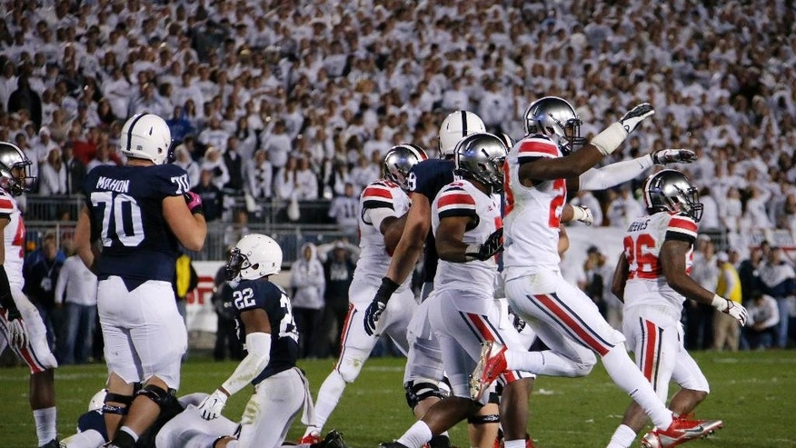 The Ohio State defense starts to celebrate after stopping Penn State on fourth down to win 31-24 in double overtime of an NCAA college football game in State College, Pa., Sunday, Oct. 26, 2014. (AP Photo/Gene J. Puskar)