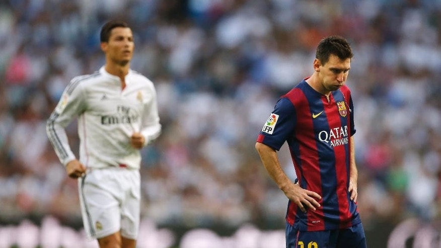 Real Madrid's Cristiano Ronaldo, left, runs as Barcelona's Lionel Messi, gestures  during a Spanish La Liga soccer match between Real Madrid and FC Barcelona at the Santiago Bernabeu stadium in Madrid, Spain, Saturday, Oct. 25, 2014. (AP Photo/Andres Kudacki)