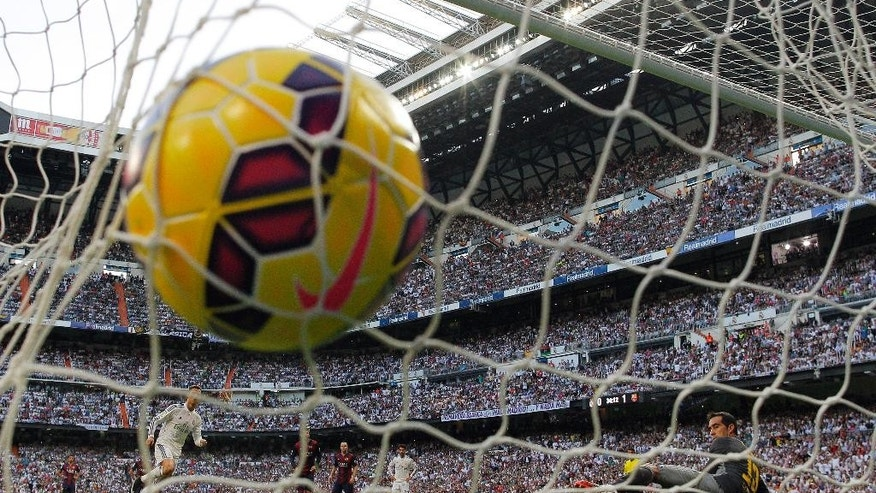 Real Madrid's Cristiano Ronaldo, left, scores his goal during a Spanish La Liga soccer match between Real Madrid and FC Barcelona at the Santiago Bernabeu stadium in Madrid, Spain, Saturday, Oct. 25, 2014. (AP Photo/Andres Kudacki)