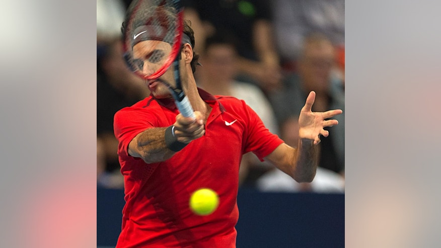 Switzerland's Roger Federer returns a ball to Belgium's David Goffin during their final match at the Swiss Indoors tennis tournament  in Basel, Switzerland, on Sunday, Oct.  26, 2014. (AP Photo/Keystone,Georgios Kefalas)