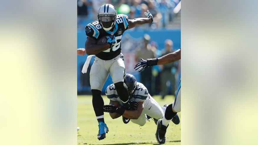 Carolina Panthers running back Jonathan Stewart (28) moves past Seattle Seahawks outside linebacker Malcolm Smith (53) during the first half of an NFL football game, Sunday, Oct. 26, 2014, in Charlotte. (AP Photo/Chuck Burton)