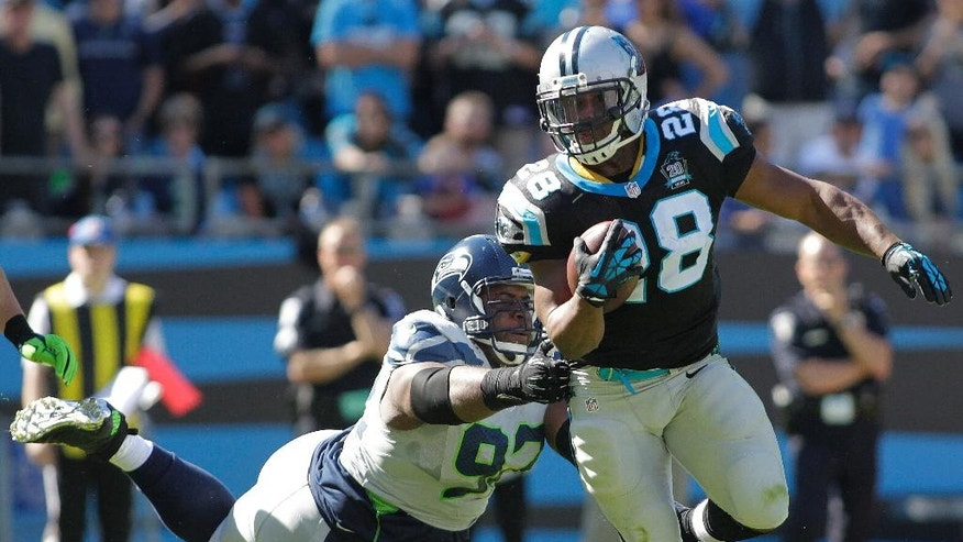 Carolina Panthers running back Jonathan Stewart (28) moves past Seattle Seahawks defensive tackle Brandon Mebane (92) during the first half of an NFL football game, Sunday, Oct. 26, 2014, in Charlotte. (AP Photo/Bob Leverone)