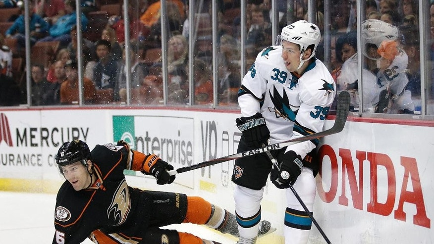 San Jose Sharks' Logan Couture, right, passes the puck as he is defended by Anaheim Ducks' Ben Lovejoy during the first period of an NHL hockey game Sunday, Oct. 26, 2014, in Anaheim, Calif. (AP Photo/Jae C. Hong)