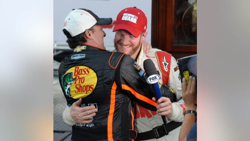 Dale Earnhardt Jr., right, gets a hug from Tony Stewart while celebrating after winning the NASCAR Sprint Cup Series auto race at Martinsville Speedway in Martinsville, Va., Sunday, Oct. 26, 2014. (AP Photo/Don Petersen)