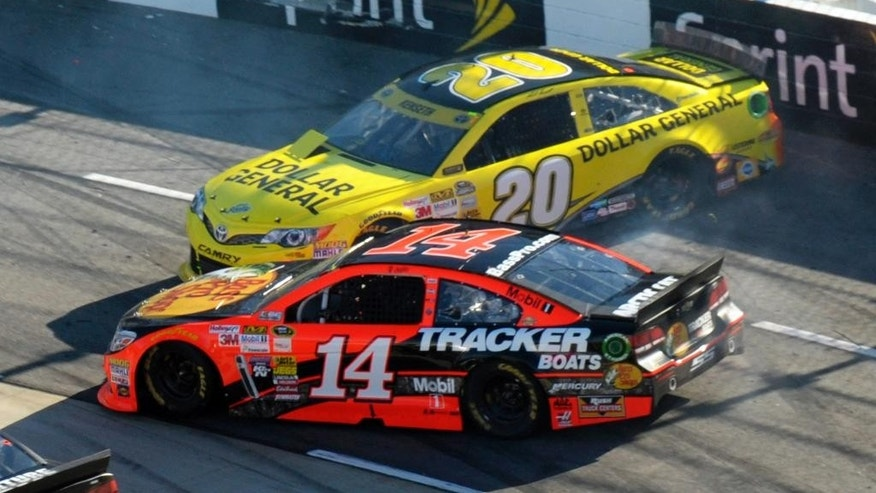 Tony Stewart (14) passes Matt Kenseth (20) during the NASCAR Sprint Cup Series auto race at Martinsville Speedway in Martinsville, Va., Sunday, Oct. 26, 2014. (AP Photo/Don Petersen)
