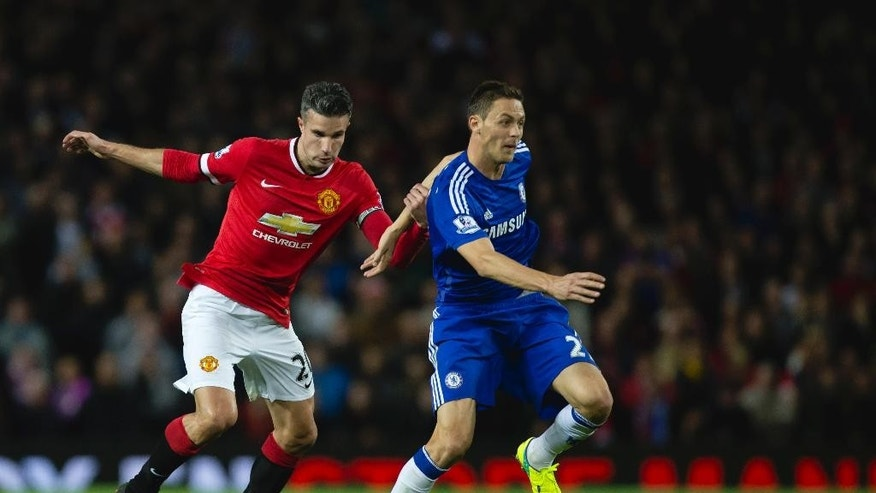 Manchester United's Robin van Persie, left, holds on to Chelsea's Nemanja Matic during the English Premier League soccer match between Manchester United and Chelsea at Old Trafford Stadium, Manchester, England, Sunday Oct. 26, 2014. (AP Photo/Jon Super)