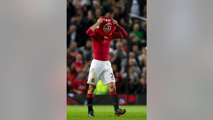 Manchester United's Robin van Persie replaces his shirt after scoring against Chelsea during the English Premier League soccer match between Manchester United and Chelsea at Old Trafford Stadium, Manchester, England, Sunday Oct. 26, 2014. (AP Photo/Jon Super)