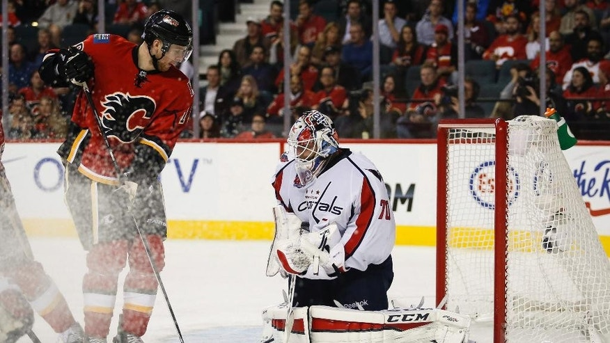 Washington Capitals goalie Braden Holtby, right, stops a shot from Calgary Flames Matt Stajan during the third period of an NHL hockey game Saturday, Oct. 25, 2014, in Calgary, Alberta. (AP Photo/The Canadian Press, Jeff McIntosh)