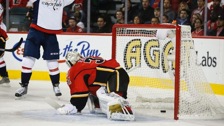 Washington Capitals' Joel Ward, left, celebrates his goal as Calgary Flames goalie Karri Ramo, from Finland, reacts during the second period of an NHL hockey game Saturday, Oct. 25, 2014, in Calgary, Alberta. (AP Photo/The Canadian Press, Jeff McIntosh)