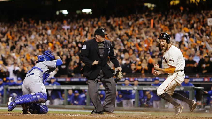 Home plate umpire Hunter Wendelstedt and Kansas City Royals Salvador Perez watches as San Francisco Giants Hunter Pence celebrates after scoring on a two-run RBI double by Juan Perez during the eighth inning of Game 5 of baseball's World Series Sunday, Oct. 26, 2014, in San Francisco. (AP Photo/Matt Slocum)