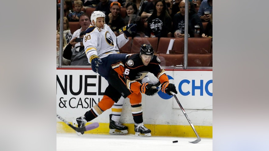 Anaheim Ducks defenseman Ben Lovejoy, right, takes the puck away from Buffalo Sabres right wing Chris Stewart during the first period of an NHL hockey game in Anaheim, Calif., Wednesday, Oct. 22, 2014. (AP Photo/Chris Carlson)