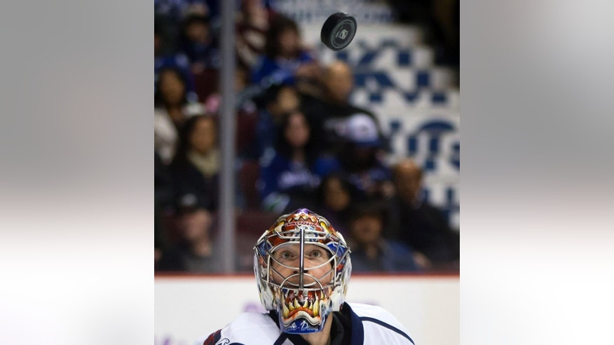 Washington Capitals goalie Justin Peters watches the puck during the first period of an NHL hockey game against the Vancouver Canucks in Vancouver, British Columbia, on Sunday, Oct. 26, 2014. (AP Photo/The Canadian Press, Darryl Dyck)