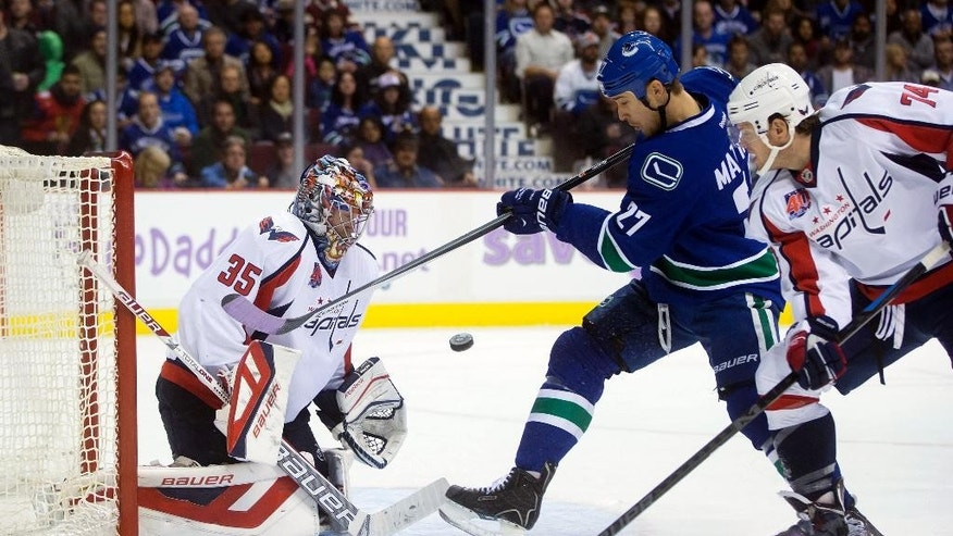 Washington Capitals goalie Justin Peters, left, stops Vancouver Canucks' Shawn Matthias (27) as Capitals' John Carlson, right, defends during the first period of an NHL hockey game in Vancouver, British Columbia, on Sunday, Oct. 26, 2014. (AP Photo/The Canadian Press, Darryl Dyck)