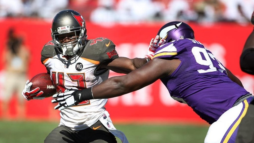 Tampa Bay Buccaneers running back Bobby Rainey (43) pushes away Minnesota Vikings defensive tackle Shamar Stephen (93) during the second half of an NFL football game on Sunday, Oct. 26, 2014, in Tampa, Fla. The Vikings won 19-13. (AP Photo/Reinhold Matay)