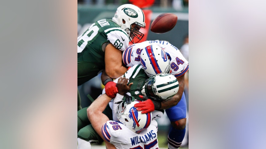 New York Jets quarterback Michael Vick (1) is sacked by Buffalo Bills' Mario Williams (94) and Kyle Williams (95) during the first half of an NFL football game Sunday, Oct. 26, 2014, in East Rutherford, N.J. (AP Photo/Kathy Willens)